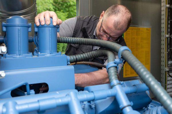 Ein Mitarbeiter überprüft den ordnungsgemäßen Zustand des Notstromaggregats