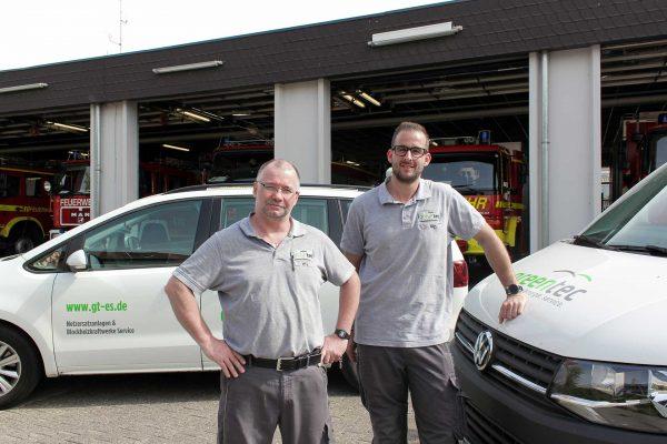 Zwei Monteure vor dem Wartungseinsatz in Ingelheim. Im Hintergrund ist die Fahrzeughalle der Feuerwehr