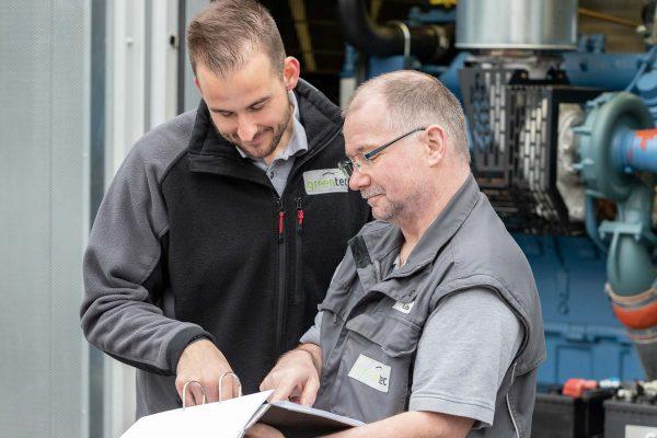 Zwei Servicemitarbeiter überprüfen das Protokoll zur anstehenden Wartung
